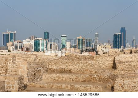 Past meets present in Bahrain as the ancient stone wall of the Bahrain Fort meets the modern skyline