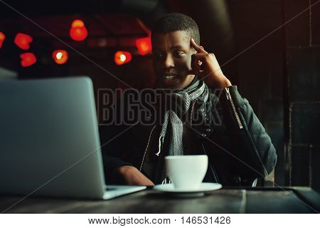 Indoor portrait of young black man sitting in cafe, drinking coffee or tea and working with lap top. Model looking at screen, expressing joyful and excitement with face. Toned.