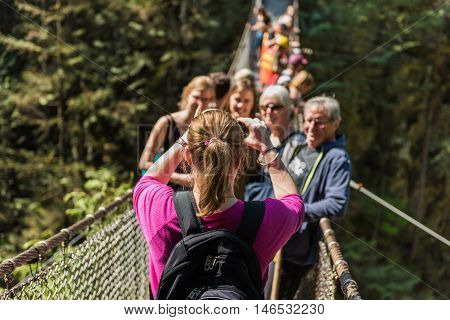 North Vancouver, Canada - 2016: People taking a group photo on Lynn Canyon Suspension Bridge