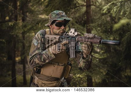Special Forces soldier with an assault rifle in the forest
