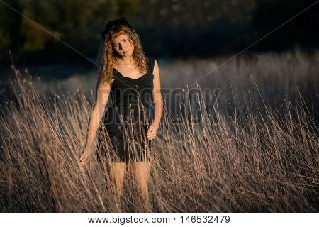 Young female standing in tall dry hay grass in black dress and red hair looking down sad