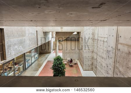 La Jolla, USA - December 10, 2015: View on courtyard with laboratory and person working on outdoor table framed through cement walls at Salk Institute, San Diego