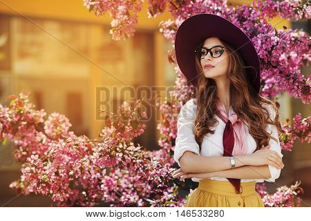 Outdoor portrait of young beautiful fashionable lady posing near flowering tree. Model wearing stylish accessories and clothes. Girl looking aside. Female beauty, fashion concept. City lifestyle. Copy space for text.