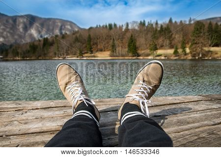 Man`s feet with shoes on the lake pier. Concept photo of relaxing at nature.