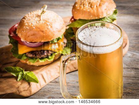 Mug of beer and two hamburgers. Toned