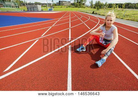 Full length portrait of tired woman holding water bottle on running tracks