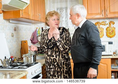 Senior couple cooking together at home kitchen