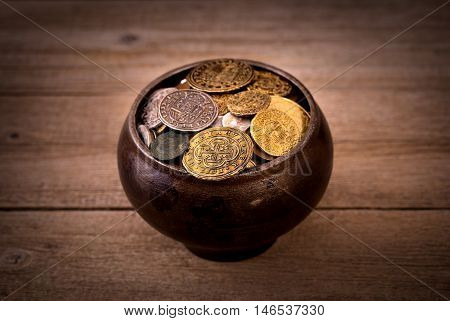 Pot of medieval golden coins on wooden background