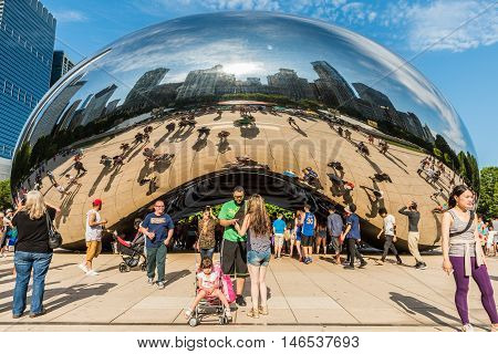 Chicago, USA - May 30, 2016: Chicago bean in Millennium Park with many people and buildings in background and families and people taking picture