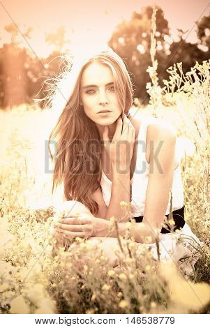 young girl sitting on a flower glade outdoors