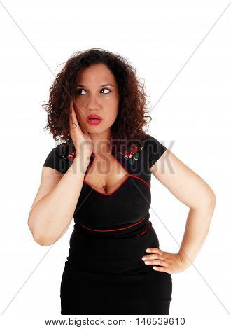 A beautiful young woman with curly brunette hair is frightened holding her hand on her head isolated for white background.