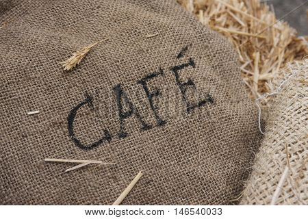 A textured burlap coffee sack marked Cafe