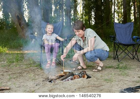 woman cooking food, people camping in forest, family active in nature, kindle fire, summer season