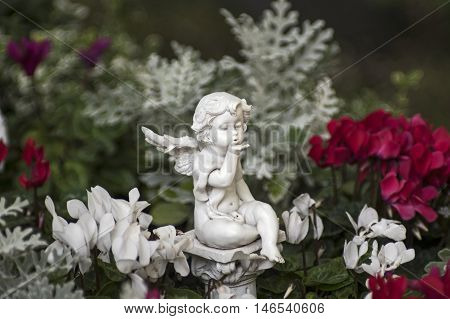 An Angel figure sitting between flowers in White and red