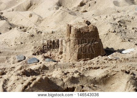 A sandcastle on the beach with some pebbles
