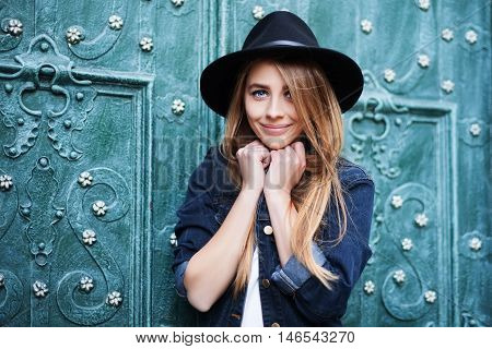 Close up street portrait of cute young smiling happy lady wearing stylish wide-brimmed hat. Model looking at camera. City lifestile.