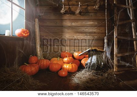 Halloween background. old wooden hut witches barn with pumpkins cobwebs magic book broom