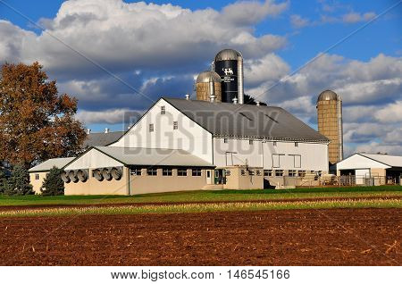 Lancaster County Pennsylvania - October 17 2015: Cattle barn with exhaust fans and three silos on an Amish farm