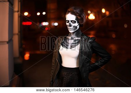 Young woman walking on avenue. Face art for Halloween party. Street portrait. Waist up. Night city background.