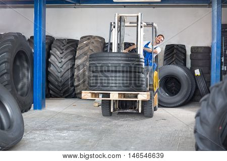 Smiling car mechanic drives a forklift in tire store