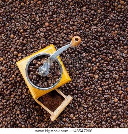 Manual coffee grinder on roasted coffee beans background