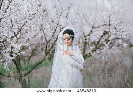 Fiancee stands in a spring flowering garden with the closed eyes bowing head to the shoulder hugging itself. The effect of film photography