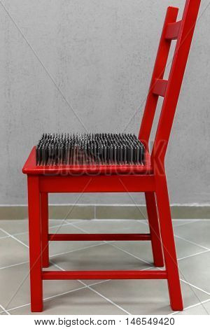 red chair with spikes on the seat. The inability to sit in a chair