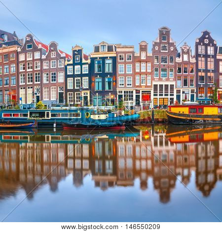 Amsterdam canal Singel with typical dutch houses and houseboats during morning blue hour, Holland, Netherlands.
