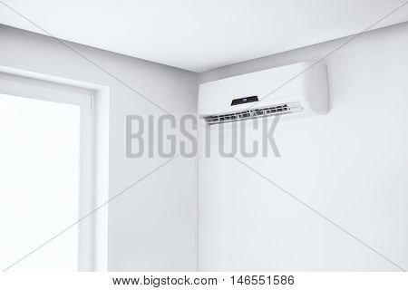 White split air conditioner on a white wall. Home interior