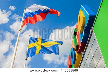 ST. PETERSBURG RUSSIA - JULY 28 2016: Russian and Sweden flags waving against the blue sky near the shopping center Mega
