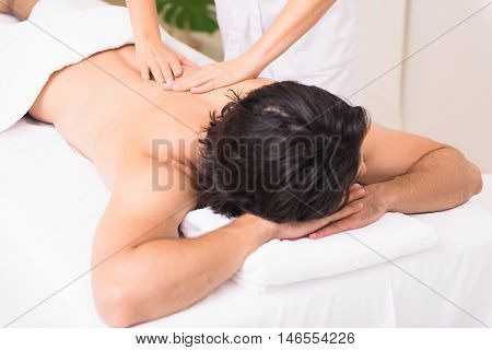 Professional masseuse massaging male back. Young guy is lying on table with relaxation