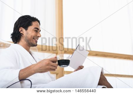 Joyful young man is relaxing in morning. He is drinking coffee and reading book. Man is sitting in bathrobe and smiling