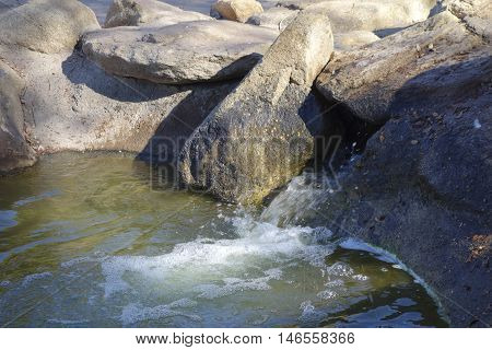 Green water flowing from decorative boulders and rocks Cortez lake small recreational park in North West Phoenix AZ
