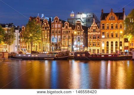 Amsterdam canal Amstel with typical dutch houses and houseboats with multi-colored reflections at night, Holland, Netherlands.
