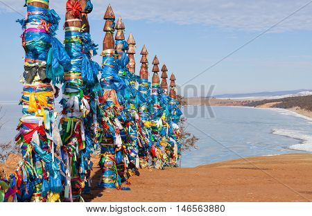 Traditional wooden poles to the hitching post serge. Prayer flags. Buryat tradition on the shores of Lake Baikal in the winter mountains in the background. Winter Landscape on Olkhon island. Buryat Region, Russia, Siberia.