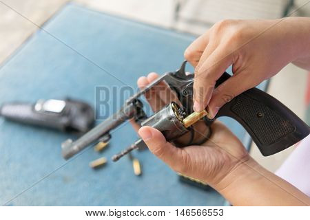 People Load Bullets Into Revolver Gun