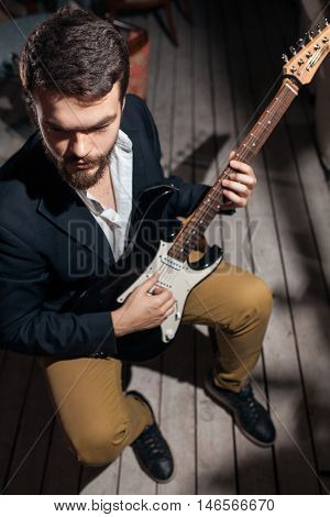 guitarist and guitar; hipster with amp sitting in chair;
