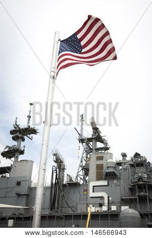 NEW YORK MAY 30 2016: The American Flag flies in front of the USS Bataan (LHD 5) at Pier 88 at the Memorial Day Commemoration ceremony on the Intrepid Sea Air & Space Museum during Fleet Week NY 2016.