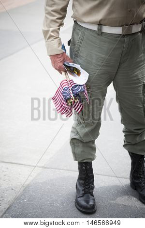 NEW YORK MAY 30 2016: Close up of a cluster of small American Flags held by a US veteran at the Memorial Day Observance service on the Intrepid Sea Air & Space Museum during Fleet Week NY 2016.