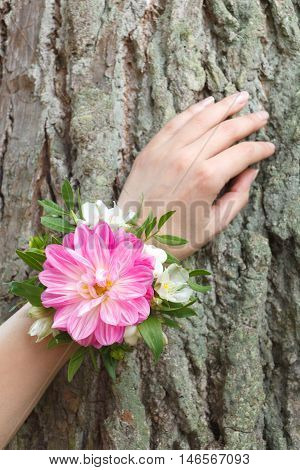 Pink, white and green wrist corsage on a hand
