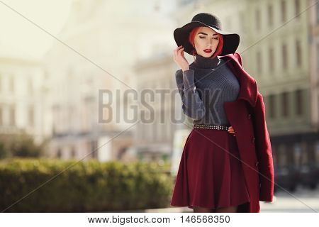 Portrait of young beautiful fashionable woman posing at street of the old city. Model wearing stylish black wide-brimmed hat, red coat. Girl looking down. Female fashion concept. Copy space. Toned