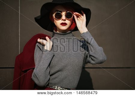 Closeup portrait of young beautiful fashionable woman with sunglasses. Lady posing on dark grey background. Model wearing stylish wide-brimmed hat. Girl looking at camera. Female fashion.Toned.