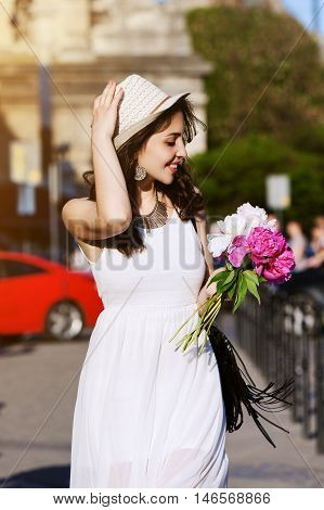 Outdoor portrait of young beautiful happy smiling lady walking on the street. Model wearing stylish white clothes and accessories. Girl looking down and aside. City lifestyle. Sunny day. Waist up.