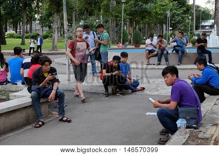 Young Asian Play Pokemon Go On Smart Phone