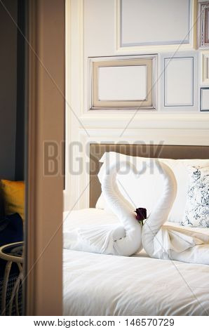 Turn down service with carefully folded swan with white towel with a red rose.