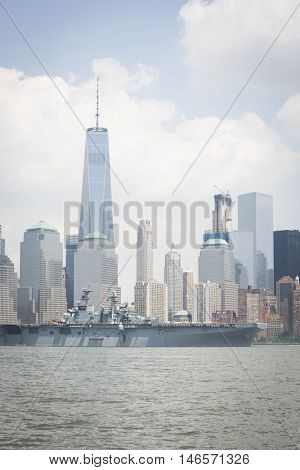 JERSEY CITY NJ - MAY 31 2016: USS Bataan (LHD 5) on the Hudson River passes the Freedom Tower upon departing Manhattan marking the end of Fleet Week 2016 as seen from Liberty State Park.