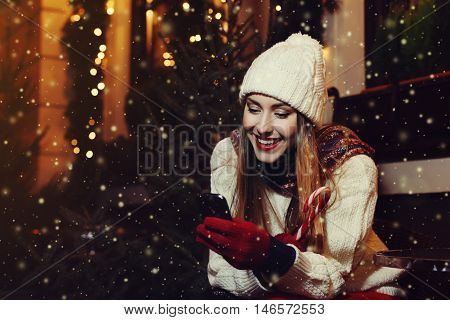 Portrait of young beautiful woman sitting in the street cafe and looking in her smartphone. Lady wearing stylish classic winter knitted clothes. Festive Christmas garland lights. Magic snowfall effect.