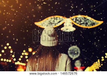 Night street portrait of beautiful young woman walking at festive Christmas fair. Back view. Lady wearing classic winter knitted clothes. Festive garland lights. Magic snowfall effect. Close up. Toned.