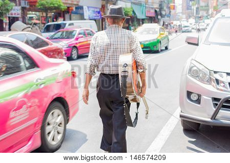 Old Man Walking On The Street Holding A Guitar.
