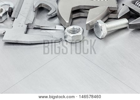 Tool Set For Hand Work Including Vernier Caliper, Wrenches And Bolts On Scratched Metallic Plate